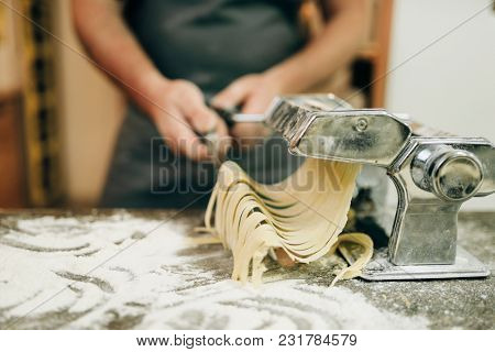 Chef cooking fettuccine in pasta machine