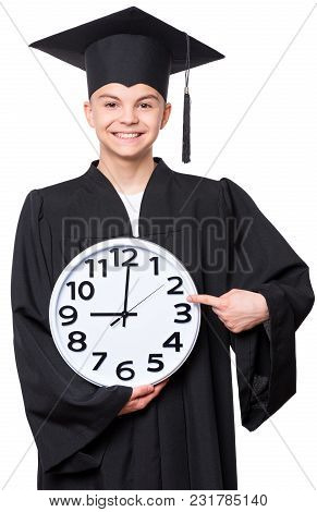 Portrait Of A Graduate Teen Boy Student In A Black Graduation Gown With Hat, Holding Big Clock - Iso