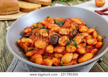 Stewed Broad Beans In Tomato Sauce With Herbs And Spices Close-up, Slices Of Rye Bread On The Wooden