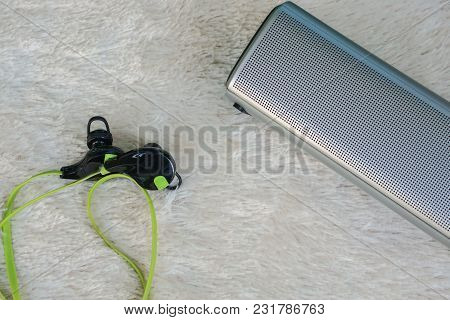 Close Up Portable Wireless Speaker With Headphones For Listening On Fur Background