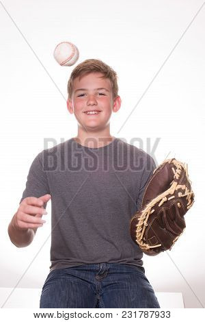 Teenage Boy Tossing Baseball In The Air With A Glove On His Left Hand. White Background.
