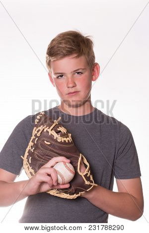 Boy With Serious Face Holding A Baseball And Wearing A Glove. White Background.
