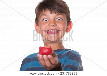 Boy Holding Out A Strawberry With Silly Face. White Background.