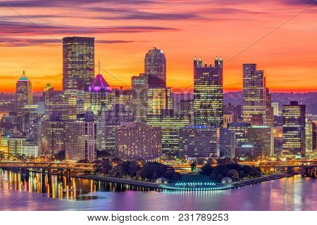 Pittsburgh, Pennsylvania, USA downtown skyline over the confluence of the three rivers at dawn.