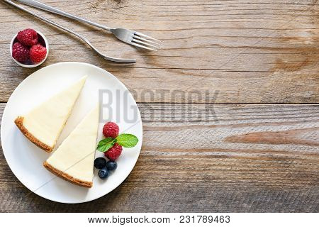 New York Cheesecake Or Classic Cheesecake With Fresh Berries On White Plate, Wooden Table Background