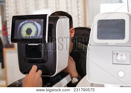 Ophthalmologist Examining Young Man With Optometric Machine In Optics Store