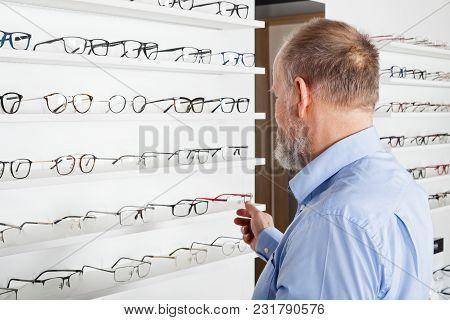 Elderly Man Choosing Corrective Glasses In Optics Store