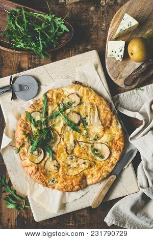 Pear Blue Cheese Quatro Formaggi Pizza Garnished With Arugula On Rustic Wood, Table Top View, Toned