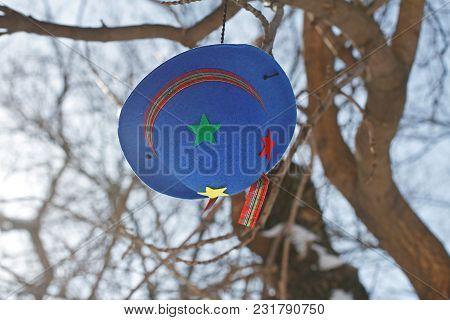 Clown's Blue Felt Hat With Colorful Stars Hanging On A Branch Of Tree
