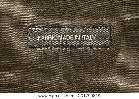 Clothes Label Lettered Made In Italy On Brown Satin Background