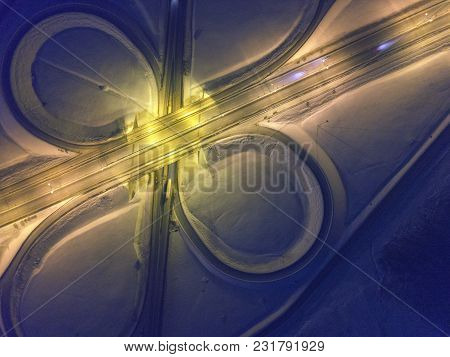 Night Aerial View Of The Lighted Road Junction On The Highway. Winter Landcape