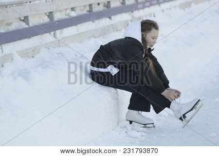 Teen Girl Sitting On Snow Tightening The Laces On The Skates, Youth Pastime And Rest