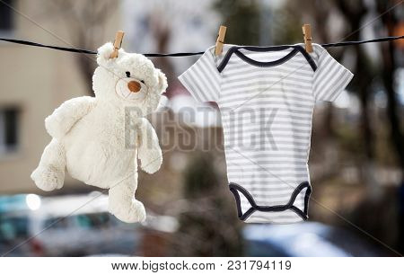 Baby clothes and teddy bear hanging on the clothesline
