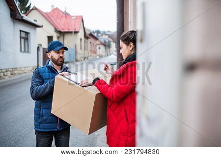 Young Woman Receiving Parcel From Delivery Man At The Door - Courier Service Concept.