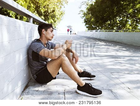 Handsome Young Runner With Smartphone In The City Park, Resting, Earphones In His Ears, Listening To