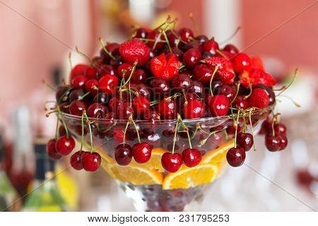 Glass Vase With Fresh Red Cherries, Strawberry And Orange. Fruit Dessert Close-up