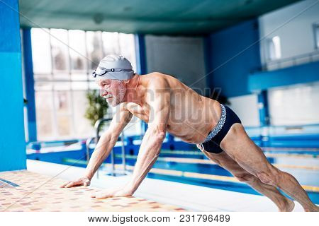 Senior Man Standing By The Indoor Swimming Pool, Stretching. Active Pensioner Enjoying Sport.