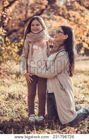 Mum And Daughter In Autumn Garden On Sunny Day. Mum Kneeing Next To Girl.