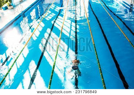 Senior Man Swimming In An Indoor Swimming Pool. Active Pensioner Enjoying Sport. Rear And High Angle