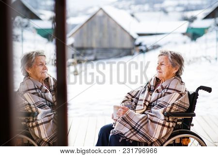A Happy Senior Woman Outside On A Terrace In Winter, Holding A Cup Of Coffee.