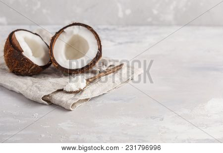 An Open Coconut With Coconut Shavings In A Wooden Spoon. Light Background, Copy Space, Vegan Meal Co