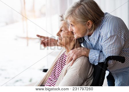 An Elderly Mother With Her Daughter At Home Looking Out Of The Window. A Carer Assisting A Disabled