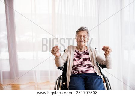 Senior Woman In Wheelchair At Home, Meditating.