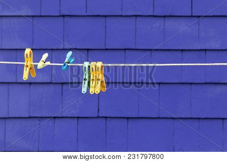 Plastic pegs on a clothesline against purple shingled wall. Space for your text.