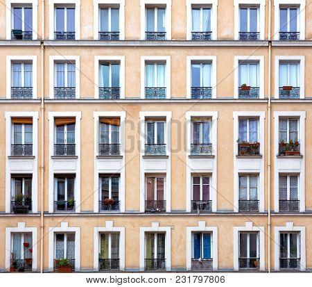 Building exterior in Paris, showing detail of newmerous windows.