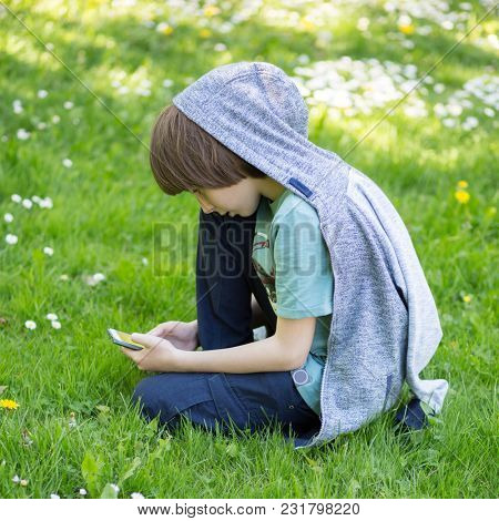 Young boy using smart phone at spring glade. Cute 11 years old boy sitting on green grass at spring park. Kid's outdoor portrait.