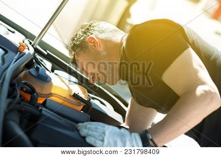 Oil change in car. Man repairing the engine in the car. Self-changing oil in own car. Man looks under the hood of his auto. Auto repair. Auto Mechanic.