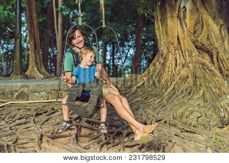 Dad And Son Swinging On An Old Swing Against The Background Of The Roots Of The Tree.