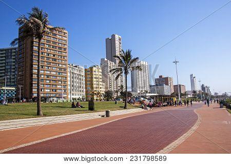 People On Paved Promenade Against City Beachfront Skyline