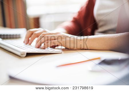 Unrecognizable Businesswoman Sitting At The Desk, Working.