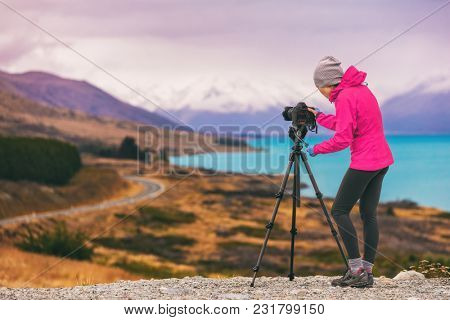 Travel photographer woman shooting nature photography mountain landscape at Peter's lookout, New Zealand. Girl tourist on adventure holiday with photo equipment, slr camera on tripod at dusk.
