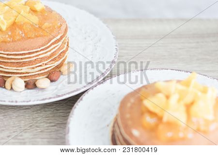 2 White Patterned Plates With Pancakes And Orange Jam And Nuts On Wooden Table Background. Closeup.