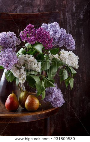 Bouquet Of Lilac Flowers And Three Pears On Old Vintage Chair.  Still Life On Dark Background.