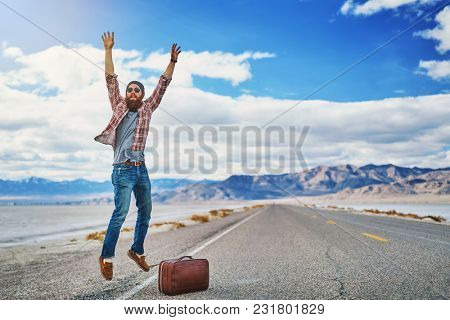 bearded hitch hiker on empty road at salt flats leaping