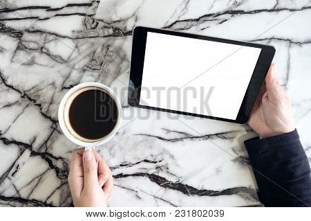 Top View Mockup Image Of Hands Holding Black Tablet Pc With White Blank Screen And Coffee Cup On Tab