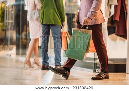 Low Section Of Stylish Man With Shopping Bags Walking Nd Couple Standing Behind In Mall