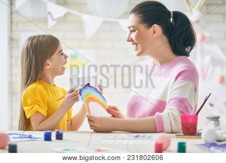 Happy family. Mother and daughter painting together. Adult woman helping to child girl.