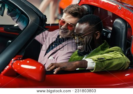 Happy Stylish Multicultural Men Sitting In New Car At Showroom