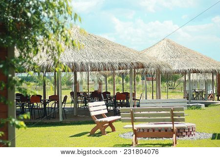 Tables And Chairs Stand Under Canopy With Thatched Roof On Green Lawn. Thatched Roof Pavilion With O