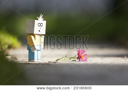 An image of a handmade sad character and a flower