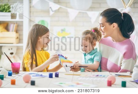 Happy family. Mother and daughters painting together. Adult woman helping to child girl.