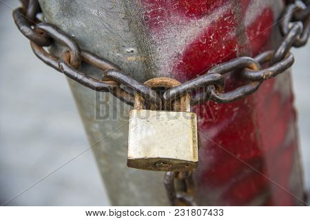 Locked Lock With The Chain Around The Post
