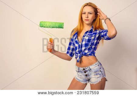 Slim Girl With Red Hair And Freckles, Holding A Green Paint Roller