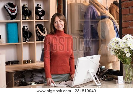 Smiling young cashier at the counter in the store