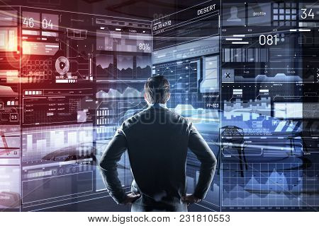 Busy Programmer. Clever Busy Young Programmer Standing In Front Of A Large Transparent Screen Of His