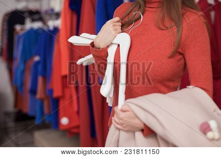 Young girl with hangers in the store